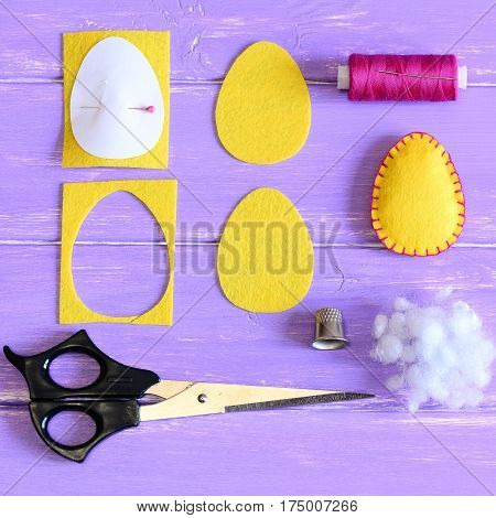 How to make cheap Easter egg. Craft guide for kids. Yellow felt Easter egg, cut felt pieces in shape of a egg, paper template, scissors, thread, thimble, filler on a wooden table. Closeup. Top view