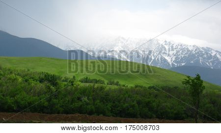 white mountains, blue hills and green foothills