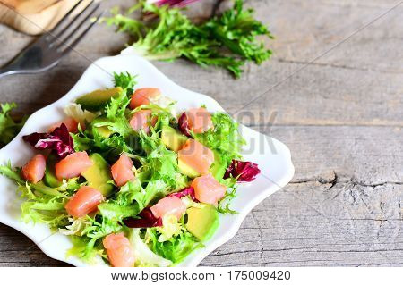 Smoked salmon, lettuce, avocado salad with lemon and olive oil dressing on a plate. Quick and delicious salmon salad recipe. Wooden background with copy space for text