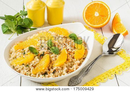 Useful fresh salad of crumbly couscous with carrots orange and mint. Dietary vegetarian food traditional Mediterranean cuisine recipes. Selective focus