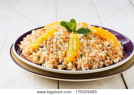 Useful fresh salad of crumbly couscous with carrots orange and mint in a bowl closeup on white wooden table. Dietary vegetarian food traditional Mediterranean cuisine recipes. Selective focus