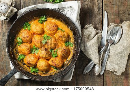 Delicious homemade meatballs stewed with sauce in the old cast iron frying pan on a wooden background. Cutlery on a linen napkin. Rustic style