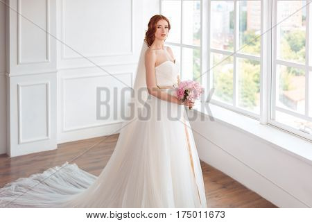 Bride in white wedding dress and long veil with bouquet of flowers indoors. Young gorgeous fashion model posing in white interior studio's room near big window in full lenght