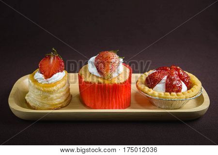 cup cake strawberry with vol au vent strawberry and mini cookies tart strawberry on brown background