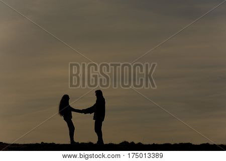 Silhouette of two people before the sundown. Silhouette of couple holding hands and turning round around.