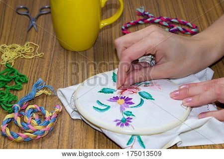Female hand embroidered cross on the canvas. Wooden table and thread stranded cotton on the background.
