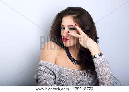 Grimacing Female Model Showing Rock V-sign Gesture In Fashion Necklace On Blue Background With Empty