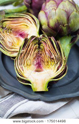 Fresh big Romanesco artichokes green-purple flower heads ready to cook seasonal food