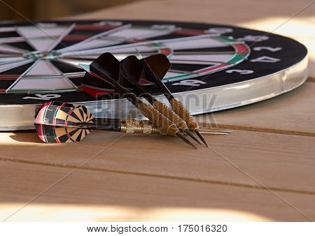 Dartboard and six darts on wooden table