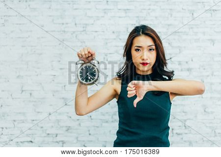 Asian Business Woman Showing Thumbs Down And Holding Alarm Clock - Indicating That Not Pleased With