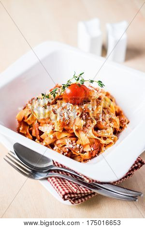 Classic pasta tagliatelle with traditional italian bolognese sauce from minced meat, carrot, celery, tomatoes served with parmesan cheese, cherry tomato and fresh thyme in a plate, selective focus