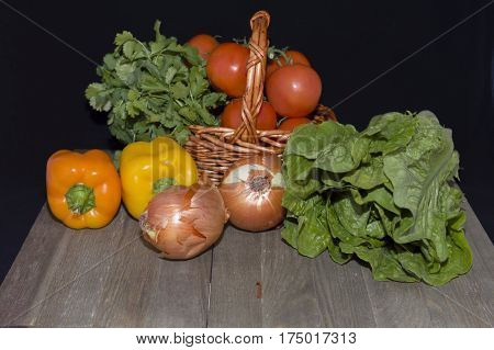 Fresh vegetables : red garden tomatoes, lettuce yellow peppers, parsley, red onion, put in small wicker basket put on dark wood table on black background