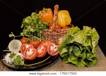 Fresh vegetables: cut in twain red tomatoes, green and yellow peppers, parsley,cut slices onion, lettuce in small wicker basket , black porcelain plate in dark wood table in black, background