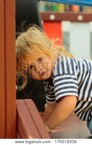 Cute baby boy with blond hair in striped blue tshirt climbing stairs in playhouse on sunny summer day outdoors on playground background