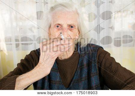 Grandma Smoking A Cigarette At Home