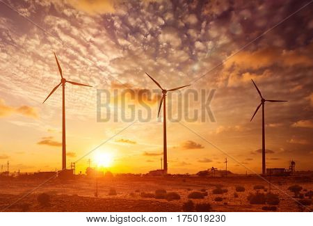 Green renewable energy concept - wind generator turbines sihouettes on sunset. With lens flare and light leak