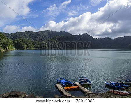 Lake and mountains landscape with colorful boats. Empty bay on volcanic lake. Sunny day on natural travel journey. Volcanic lake surrounded by forest mountains. Sunny weather and wild nature scene