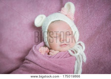 Smiling newborn baby sleeps in a hat with ears on a pink blanket