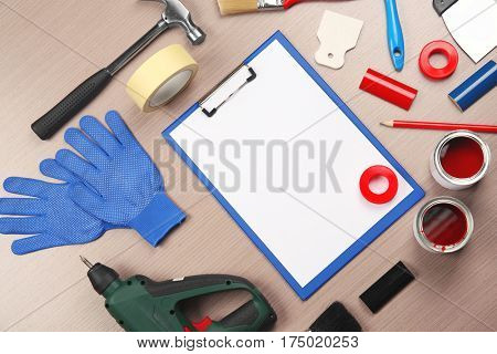 Clipboard and decorator tools on wooden table