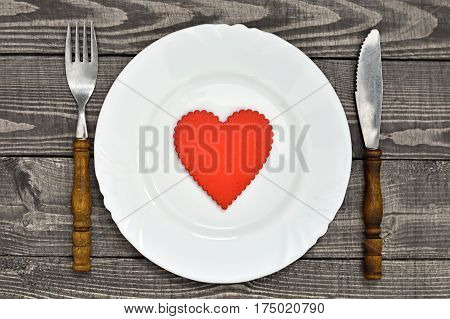 Valentines Day table setting with plate decorated with heart ornament and silverware