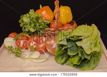 Fresh vegetables : red garden tomatoes,cut twain red tomatoes, cut twain red onion yellow peppers, lettuce, parsley put in small wicker basket in light cutting board wood in black background