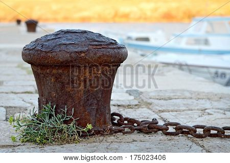 Close up of old rusty mooring bollard
