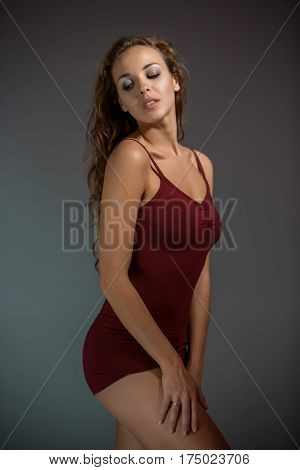 Young beautiful woman in red T-shirt and shorts dancing on a dark gray studio background. Modern, Contemporary, improvisation