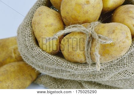 Potatoes in sack bag on white background.