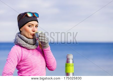 Woman athlete fit girl wearing warm sporty clothes outdoor in cold weather drinking hot tea from vacuum flask thermos warming up. Sports activities hiking in winter or autumn time