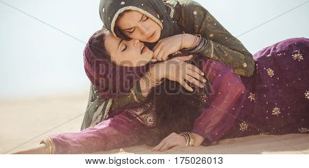Desert women thirsty dehydrated lying on sand outdoors. Dehydration, overheating, thirst and heat stroke concept image with two sisters in desert nature.Portrait of two beautiful mixed race asian caucasianl arabian girls lost in desert during journey. poster
