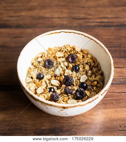 Homemade granola or muesli with oat flakes, corn flakes, dried fruits and toasted peanuts with fresh black currant and black raspberry in a bowl for breakfast, selective focus