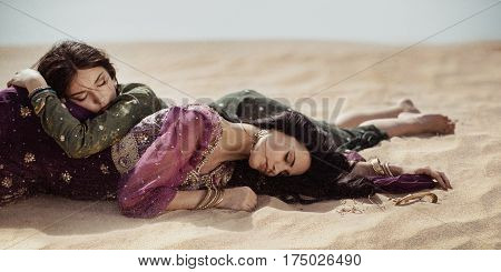 Desert women lying on sand outdoors. Dehydration, overheating, thirst and heat stroke concept image with two sisters outdoors in the nature. Two arabian girls lost in desert during journey. Windy weather