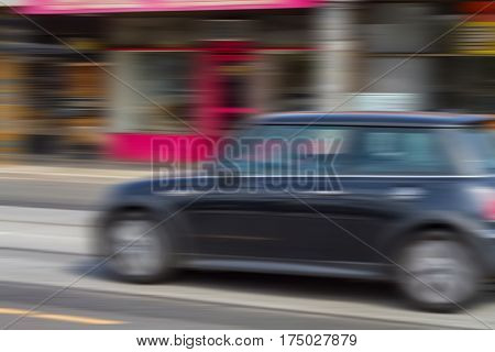 Panning photograph of a Mini Cooper car in the city with abstract motion blur