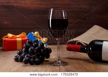 Red wine bottle. Wineglass with dark grapes branch. Gift box with bow on rustic wooden background.
