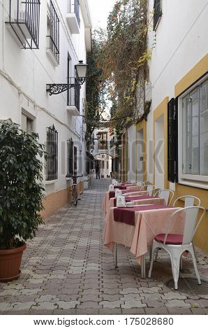 MARBELLA, SPAIN - FEBRUARY 27, 2017: Tables at a street of the historic center of Marbella a city of the province of Malaga Andalusia Spain.