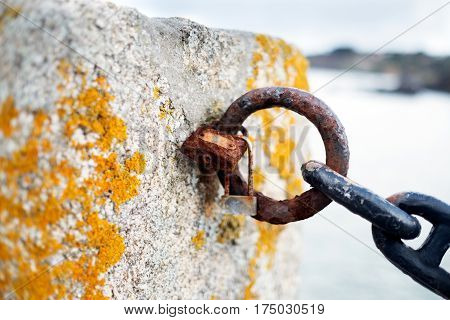 Paddles and chain rotten by the sea saltpetre in the battlement of a medieval castle on an island near La Coruna Galicia Spain