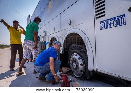 Puerto Suarez, Bolivia on August 21, 2015: Mechanic changing flat tire at bus breakdown