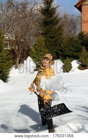 Woman throwing snow in the garden with a shovel