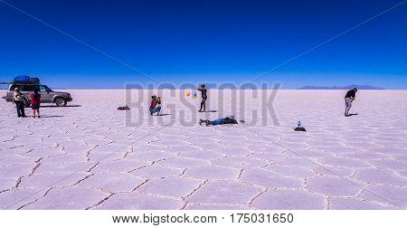 Salar de Uyuni, Bolivia on September 21, 2015: Tourists next to jeep taking funny photos on the salt lake