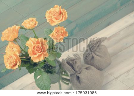 Bouquet of yellow roses in glass vase with two burlap bags over old wooden background