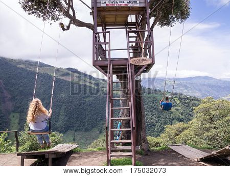 Banos, Ecuador on November 18, 2015: Tourists enjoying the giant swing at the treehouse Casa del Arbol in the Andes near Banos, Ecuador. The view from the swing is breathtaking.