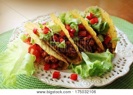 Mexican food - tacos with meat, lettuce and tomatoes on plate