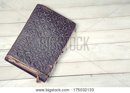 Old photo album on white wooden background