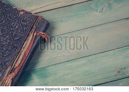 Old photo album on dark green wooden background