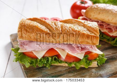 Two halves of baguette sandwiches with lettuce, tomatoes, cheese