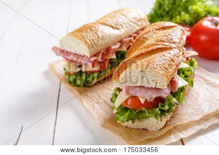Two halves of baguette sandwiches with ham, lettuce, tomatoes and cheese.