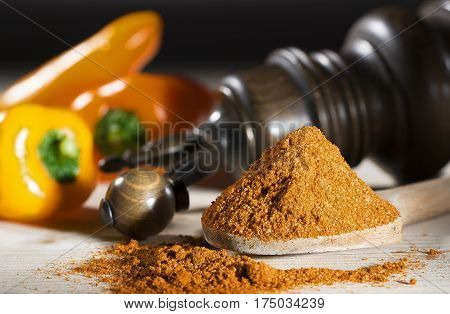 Ground pepper mill  yellow pepper on a table with paprika and pepper mill