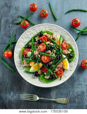 Fresh Tuna Green Bean salad with eggs, tomatoes, beans, olives on white plate. concept healthy food.