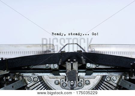 ready. steady. go. slogan taped words on a vintage typewriter on white blank page