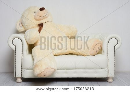 Big beige toy bear has rest on white leather sofa